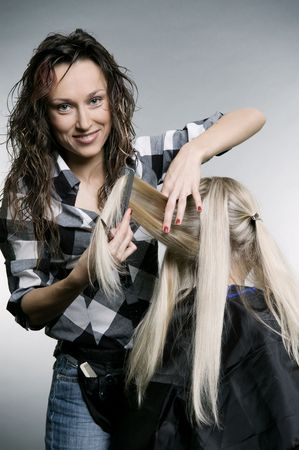 smiley hairdresser doing hairstyle. studio shot Stock Photo - 3724465