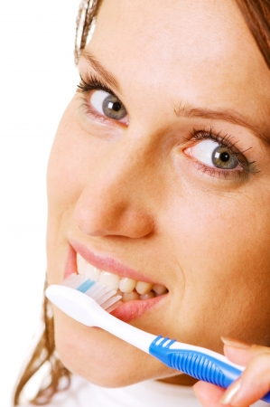closeup of woman with toothbrush over white photo