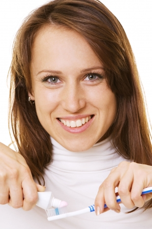 smiley woman with toothpaste and toothbrush over white photo