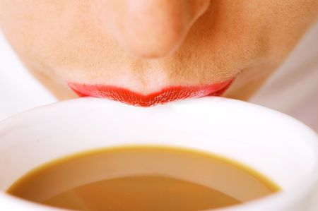 women holding cup: woman lips on cup of coffee with milk