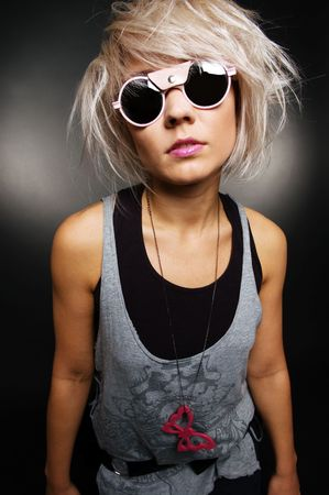fashionably: portrait of stylish casual girl in sunglasses over dark background