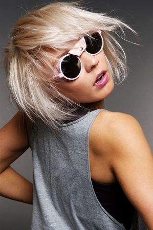 woman in funny sunglasses turning. portrait over grey background photo
