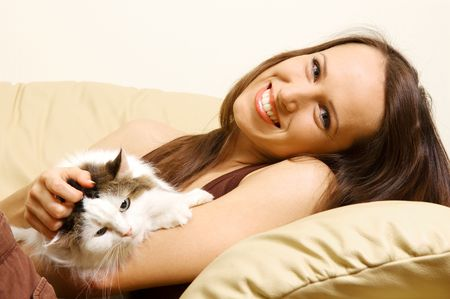 happy woman lying on the sofa with her cat photo