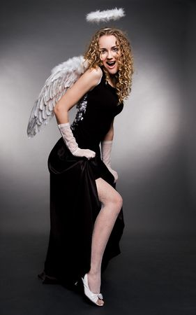 attractive angel in stockings showing her leg over dark background photo