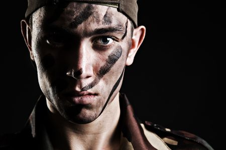 army face: portrait of young soldier in camouflage against black background Stock Photo