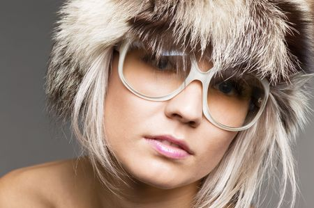 pretty blond model in fur hat and sunglasses over grey background photo