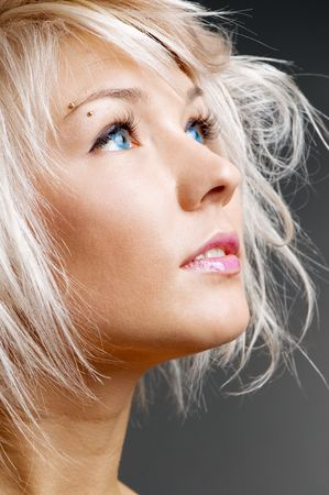 pretty blond with blue eyes looking at something. studio portrait over grey background