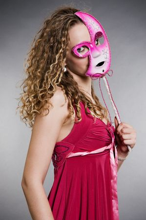 pretty woman in pink mask over grey background photo