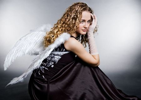 angel girl: sad angel sitting on the floor Stock Photo