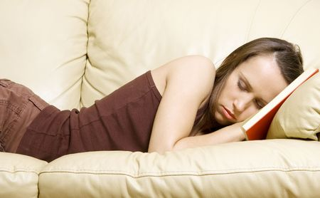 young woman sleeping on book at home photo