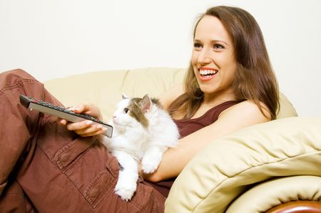 smiley woman watching tv with her cat