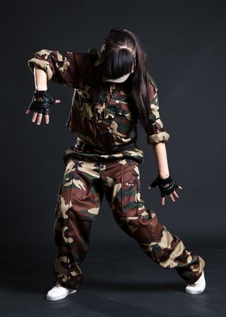 young woman dancing in camouflage over dark background
