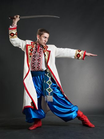 armed cossack posing against dark background photo