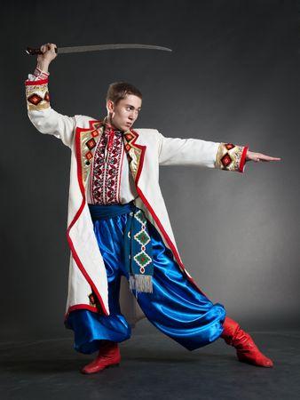 sabre: armed cossack posing against dark background