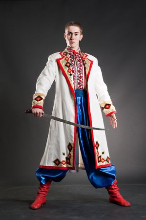 armed young cossack in national ukrainian dress over dark background photo