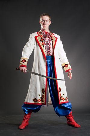 sabre: armed young cossack in national ukrainian dress over dark background