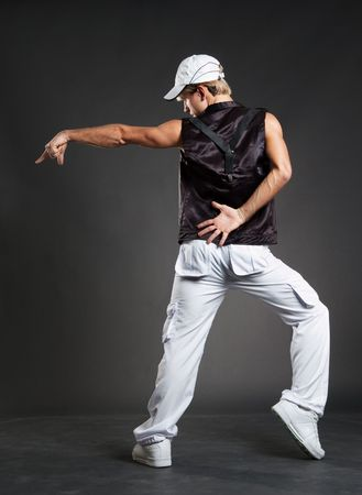 hip-hop dancer in dance pointing against dark background photo