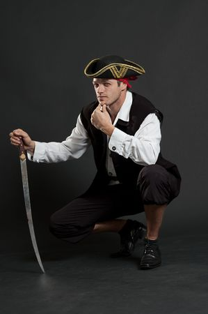 sabre: serious pirate with sabre sitting against dark background Stock Photo