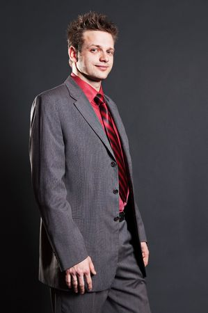 earnest: successful businessman in grey suit over dark background Stock Photo