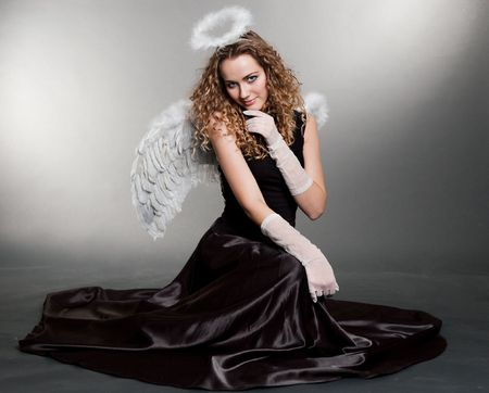 sweet angel sitting on the floor over grey background photo