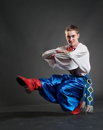 young cossack dancing over dark background photo