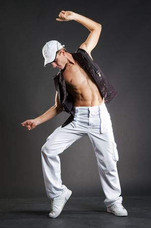 attractive dancer in white cap posing against dark background photo