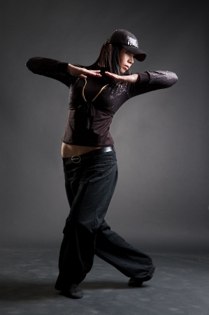 attractive hip-hop girl dancing  against dark background photo