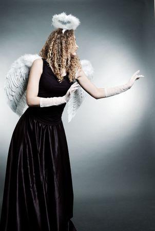 beautiful angel in black dress against grey background photo