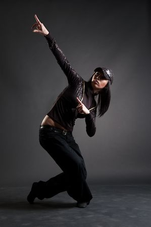 beautiful brunette dancing against dark background photo