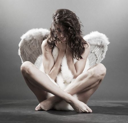 beautiful angel with white furs over dark background Stock Photo
