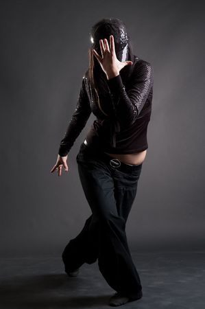 cool girl dancing against dark background photo