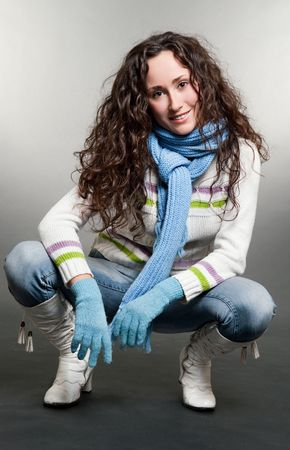 curly brunette in scarf and gloves sitting on the floor photo