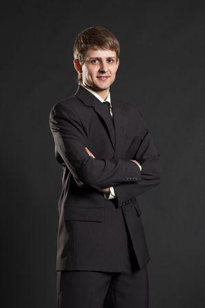 earnest: serio hombre de negocios en traje negro contra el fondo oscuro Foto de archivo