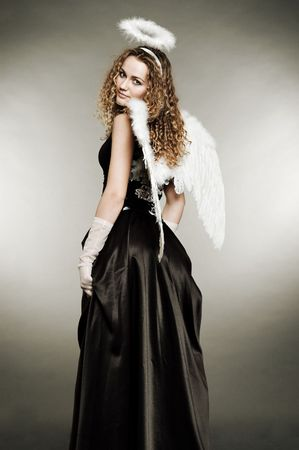 fairy-tale angel in black dress against grey background photo