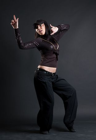 hip-hop dancer in black clothes posing over dark background photo