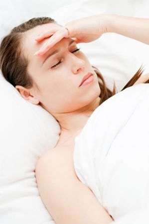 afflict: young woman with headache in her bed