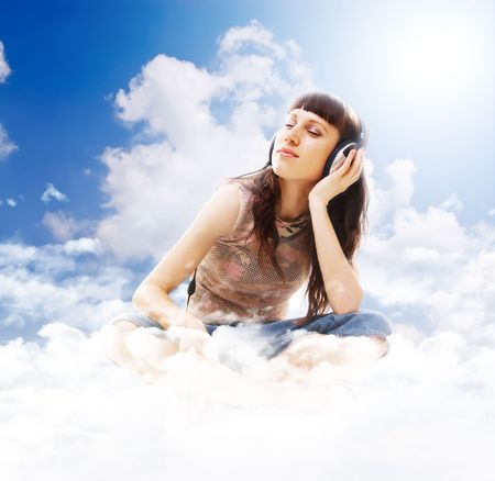 beautiful teenage listening music with pleasure on the clouds photo