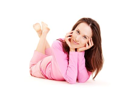smiley young girl lying in pink pyjamas over white background photo