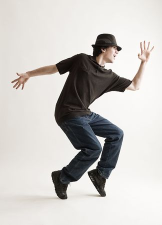 stylish man in hat dancing against grey background