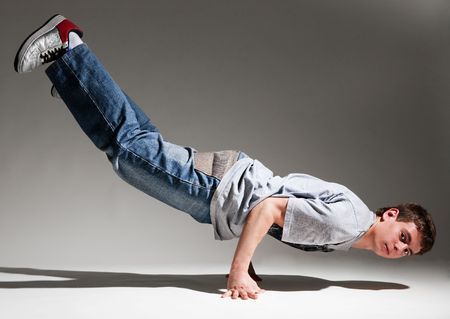 roughneck: breakdancer balancing on his hands against grey background