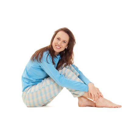 smiley woman in blue pajamas sitting on the floor. isolated on white photo