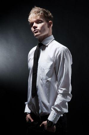 attractive fashionable man against dark background photo