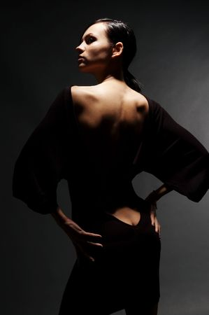 fashionably: sexy woman in dress with back against dark background