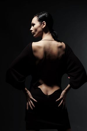 lean back: glamor woman in dress with back over black background Stock Photo