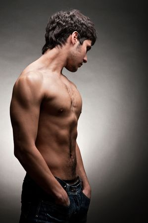 adult man with torso posing against dark background