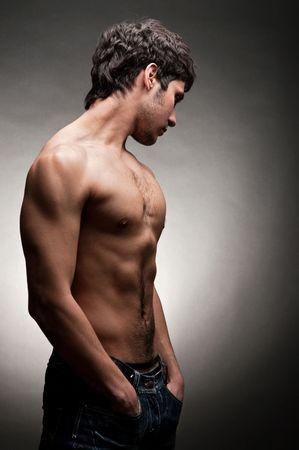 m�lancolie: homme adulte en posant torse nu contre le fond sombre