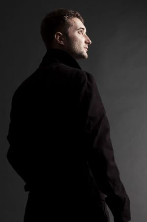 handsome adult man in black coat looking up Stock Photo