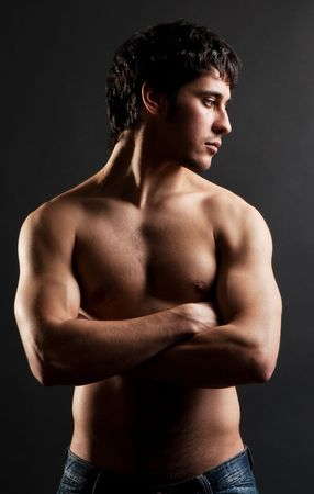 the tempter: portrait of handsome thoughtful man with torso against dark background