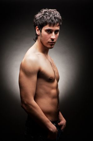 pecs: portrait of handsome young man against dark background