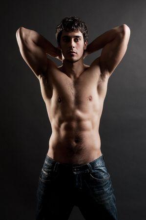 the seducer: portrait of handsome muscleman against dark background